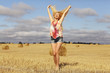 beautiful blonde jumps in sloping field sun happiness
