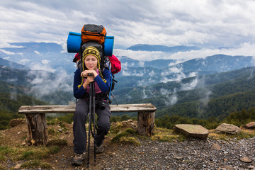 Woman backpacker sitting mountain bench.