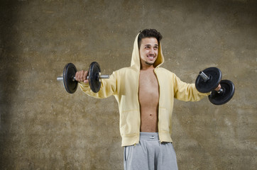 Young man training with dumbbells at indoor