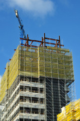Construction site with office building in scaffolding and crane