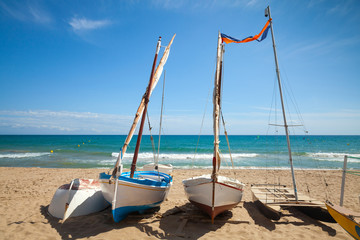 Small sailing boats lay on the sandy beach in Calafell town
