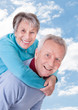 Senior Man Giving Piggyback Ride To Woman Against Sky