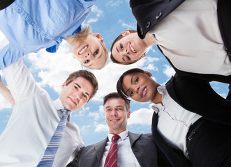 Multiethnic Business People Forming Huddle Against Sky