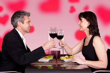 Couple Toasting Wineglasses At Table In Restaurant
