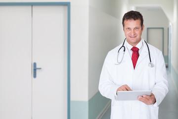 Doctor Using Digital Tablet In Hospital Corridor