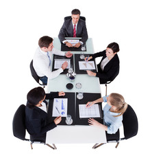 Businesspeople Discussing Over Graphs At Conference Table