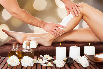 Male Beautician Waxing Woman's Leg In Spa
