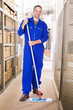 Smiling Worker Cleaning Warehouse With Mop