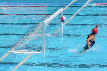 A water polo goalkeeper misses the ball going into the net of th