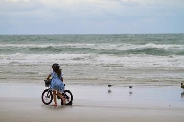 Girl walking with her bike along the beach