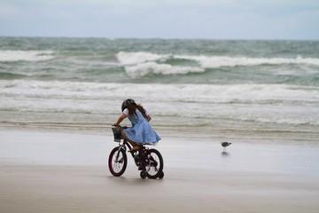 Girl riding her bike on the beach