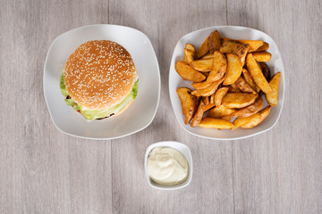Delicious Burger And Fried Potatoes Served In Plates