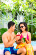 Asian couple drinking  cocktails at pool