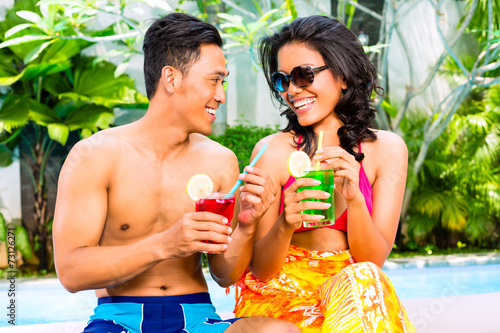 canvas print picture Asian couple drinking  cocktails at pool