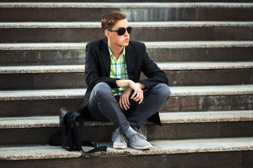 Young fashion man sitting on the steps