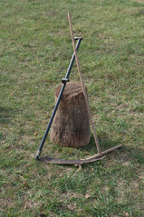 Rake and scythe in the garden left on a tree trunk