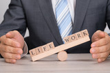 Businessman Covering Imbalance Between Life And Work On Seesaw poster