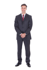 Businessman With Hands Clasped Standing Against White Background