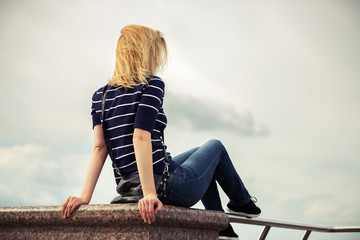 Young fashion woman sitting against a cloudy sky