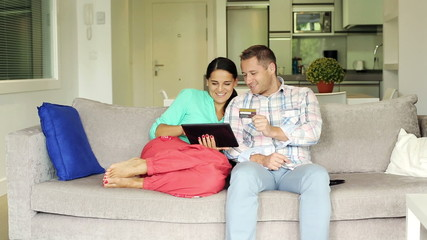 Couple doing online shopping with tablet computer sitting on sof