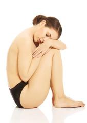 Nude woman in panties sitting on the floor