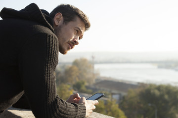 Attractive Man Holding The Mobile Phone Outdoor