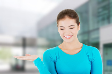 Happy , excited young woman presenting copy space