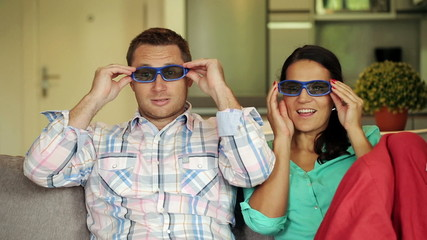 Happy, excited couple watching 3D movie on sofa at home