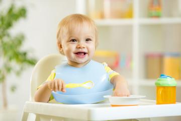 happy baby kid boy eating food itself with spoon