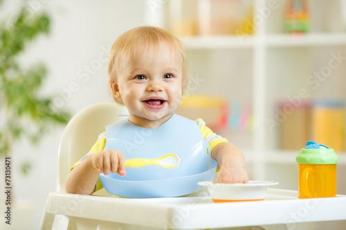 happy baby kid boy eating food itself with spoon - 73130471