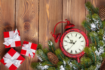 Christmas clock over wooden background with snow fir tree and gi