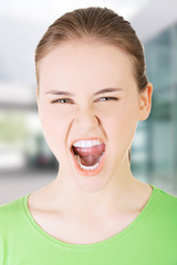 Young casual woman screaming with anger