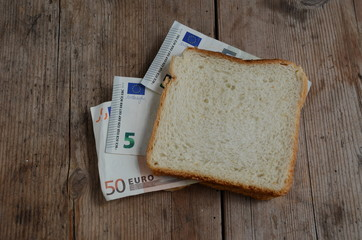 slice white bread with euro money banknotes