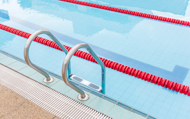 The view of metallic ladder of swimming pool with marked lanes.