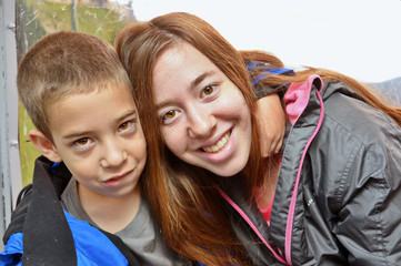 Portrait of brother and sister hugging in a cable car