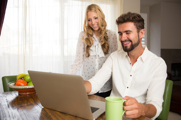Couple watching a video on the pc in the kitchen