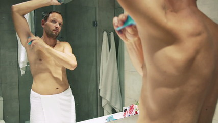 Man in towel applying antiperspirant after shower