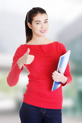 Attractive smiling woman gesturing thumb up