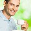 Portrait of young happy smiling man drinking coffee, outdoors