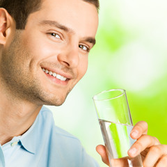Young cheerful man with glass of water, outdoor