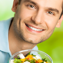 Portrait of cheerful smiling man with salad, outdoor