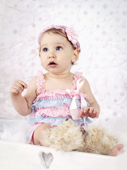 Beautiful little baby girl with plush teddy bear