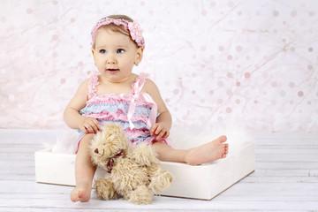 Stunning little baby girl with teddy bear