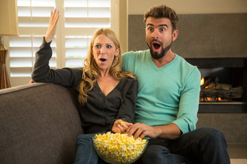 Cute couple watching a comedy at home