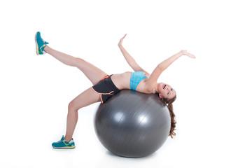 Junge Frau hat Spaß auf Gymnastikball und lacht