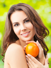 Young woman with persimmon fruit, outdoor