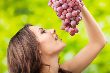 Portrait of woman with grapes, outdoors