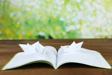 Origami boats on notebook on wooden table,  outdoors