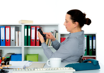 businesswoman using her smartphone at the workplace