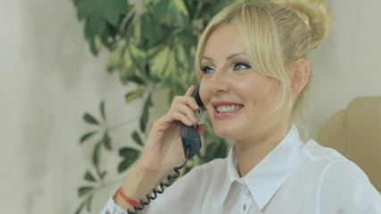 Attractive blonde woman talking on the phone in office